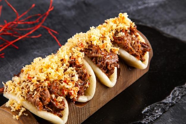 Sluit omhoog op gua bao, gestoomde broodjes met vlees. bao geserveerd met lekker beleg op donker. aziatische keuken. aziatische sandwich gestoomde gua bao. fast food in japanse stijl. selectieve aandacht
