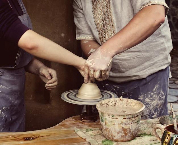 Sluit omhoog op handen die een kom op een pottenbakkersschijf creëren