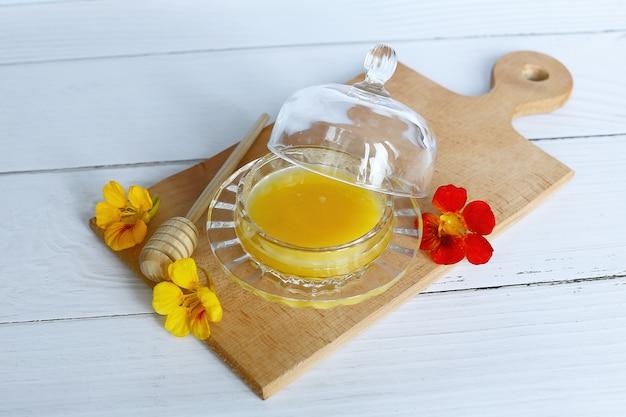 Sluit omhoog op honing in glaskom met bloemen