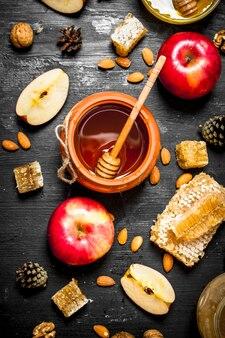 Sluit omhoog op honing in pot met plakjes rijpe appels en noten