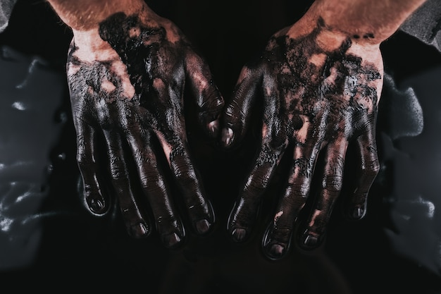 Sluit omhoog op iemands handen in zwarte verf