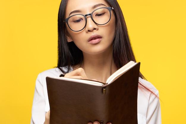 Sluit omhoog op jonge aziatische vrouw die een notitieboekje houdt