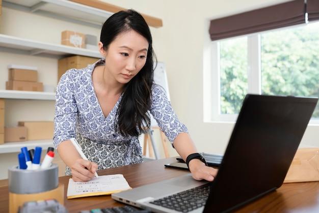 Sluit omhoog op jonge vrouw die informatie op laptop controleert
