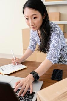 Sluit omhoog op jonge vrouw die informatie op laptop schrijft