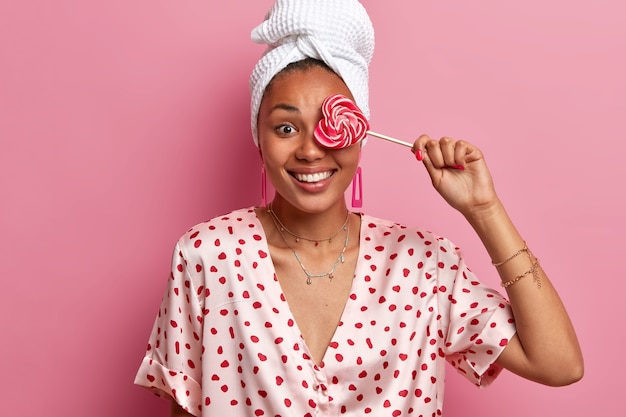 Sluit omhoog op jonge vrouw die kleed en verpakte handdoek op hoofd draagt