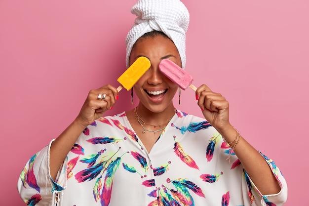 Sluit omhoog op jonge vrouw die kleed en verpakte handdoek op hoofd draagt Gratis Foto