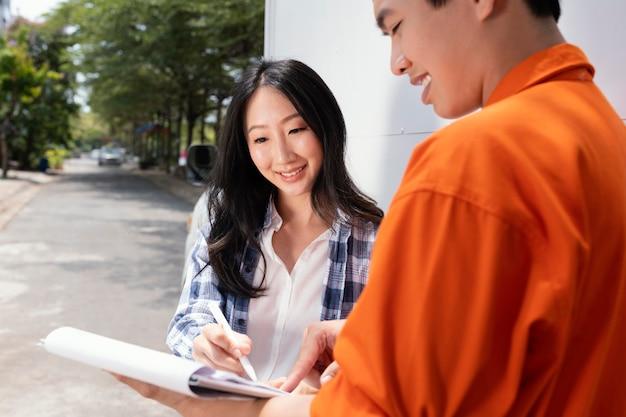 Sluit omhoog op jonge vrouw die voor pakketlevering ondertekent