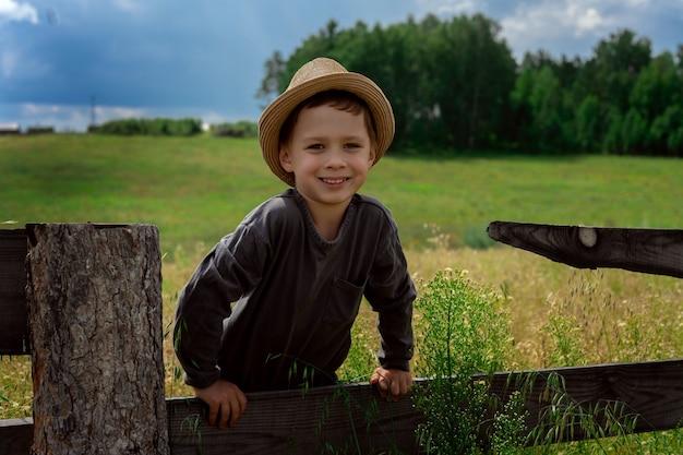 Sluit omhoog op jongen met hoedenzitting op het hek