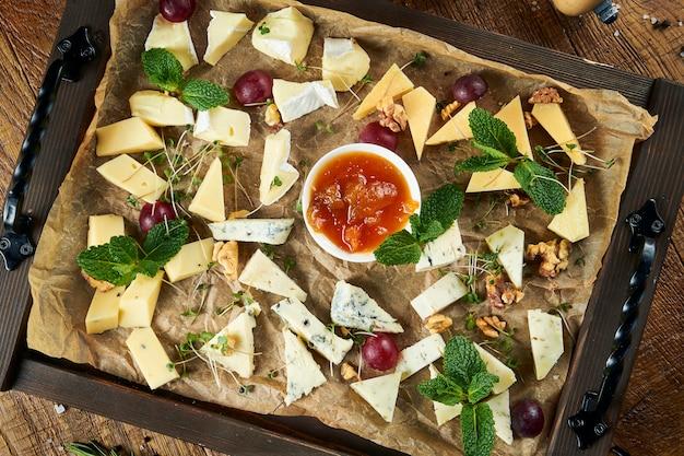 Sluit omhoog op kaasplaat die met noten, druiven, honing wordt gediend. bekijk van bovenaf op verschillende soorten kaas op donkere ondergrond met kopie ruimte. diverse kazen