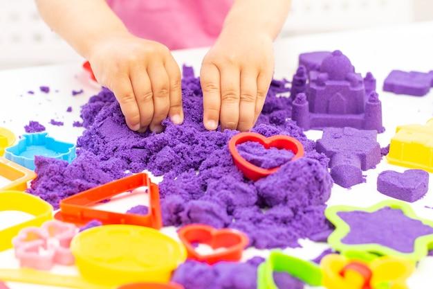 Sluit omhoog op kindhanden die met kleurrijk kinetisch zand spelen