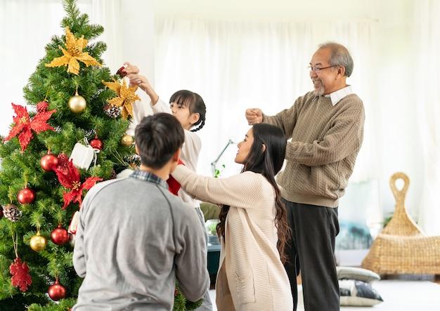 Sluit omhoog op klein aziatisch meisje dat een kerstboom met ornamenten verfraait