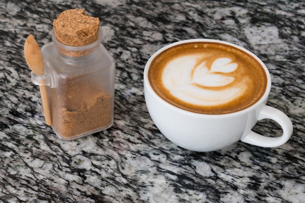 Sluit omhoog op koffie latte art met bruine suiker