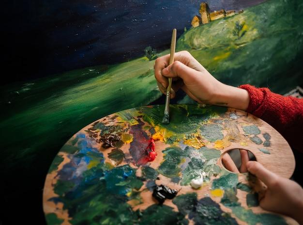 Sluit omhoog op kunstenaarshanden die een kleur kiezen om te schilderen