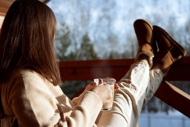 Sluit omhoog op meisjeszitting met koffie op de veranda en kijkend naar het bos
