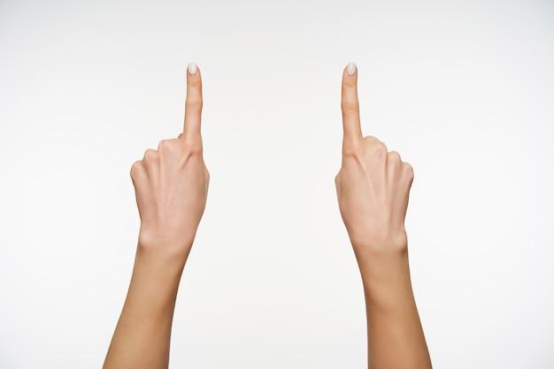 Sluit omhoog op mooie handen terwijl u de wijsvingers omhoog houdt terwijl u omhoog wijst