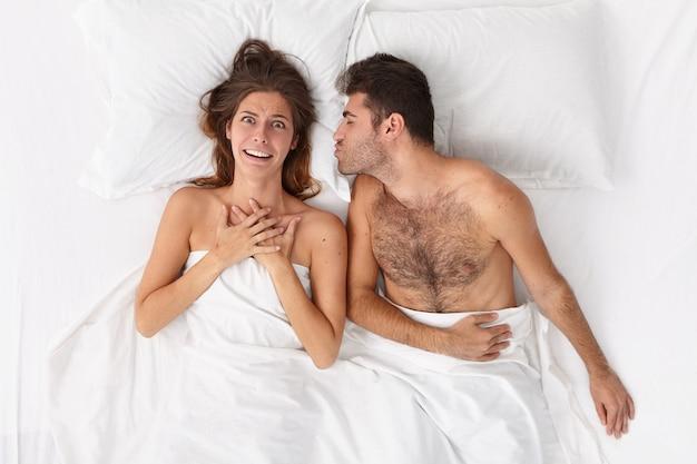 Sluit omhoog op paar dat in bed onder witte deken ligt