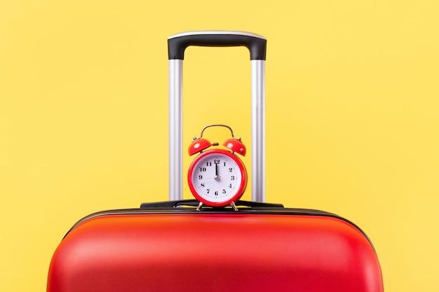 Sluit omhoog op rode koffer met een rode geïsoleerde klok