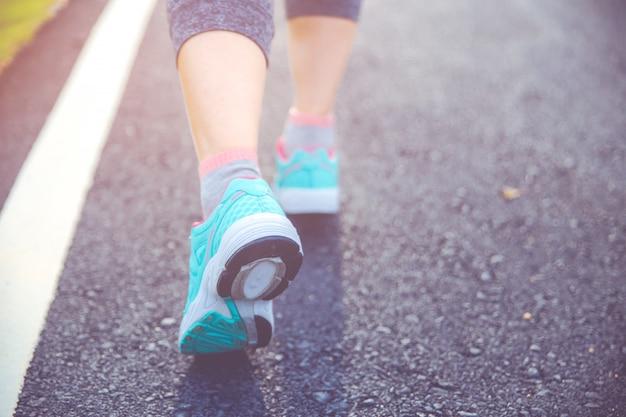 Sluit omhoog op schoen, de voeten die van de agentatleet op weg onder zonlicht in de ochtend lopen.