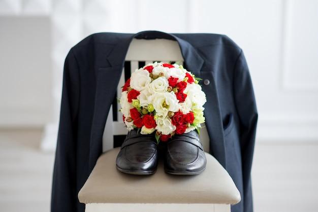Sluit omhoog op schoenen met bloemboeket en jasje op de stoel