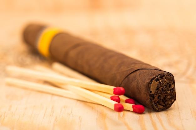 Sluit omhoog op sigaar en vijf overeenkomsten met rode hoofden