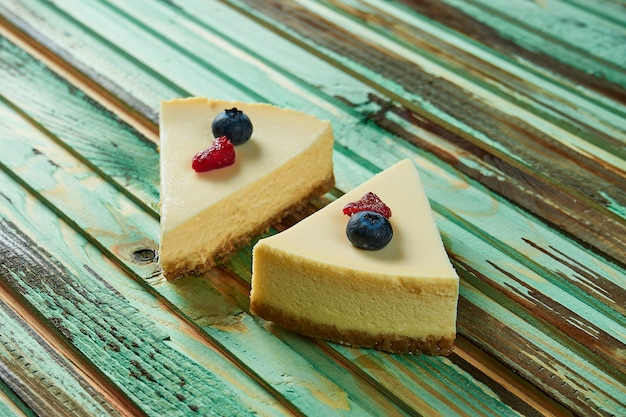Sluit omhoog op smakelijke plak van delicate airy cheesecake op houten lijst. heerlijke dessertcake na het eten. eten fototafel voor recept of menu