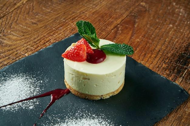 Sluit omhoog op smakelijke plak van delicate airy cheesecake op houten oppervlakte. heerlijke dessertcake na het eten. de fotoachtergrond van het voedsel voor recept of menu