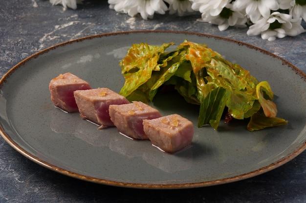 Sluit omhoog op smakelijke tonijn met sla in saus