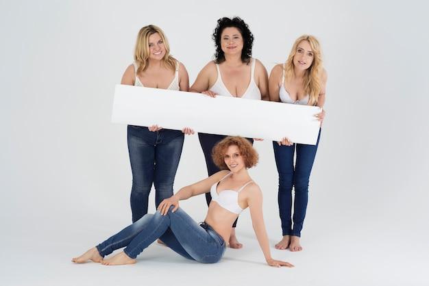 Sluit omhoog op volwassen vrouwen die jeans dragen en wit aanplakbord houden