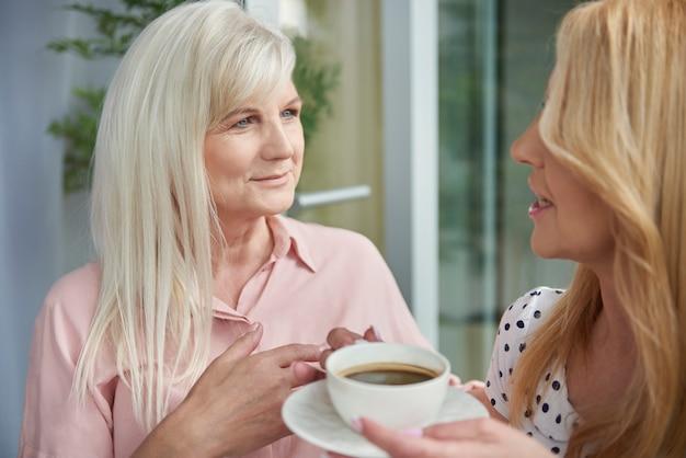 Sluit omhoog op volwassen vrouwen die van goede koffie genieten op het balkon