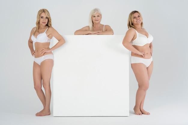 Sluit omhoog op volwassen vrouwen in ondergoed met leeg aanplakbord