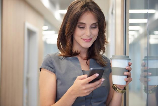 Sluit omhoog op vrouw die koffie drinkt en de telefoon exploiteert