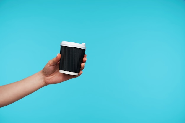 Sluit omhoog op zwarte document kop met koffie die met de hand wordt gehouden