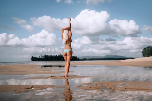 Sluit omhoog openlucht geschotene jonge sexy blonde vrouw in blauwe bikini, zonnebadende op zee kust. oceaan strand. perfect slank lichaam en kont met zand. vakantie en reizen. thailand
