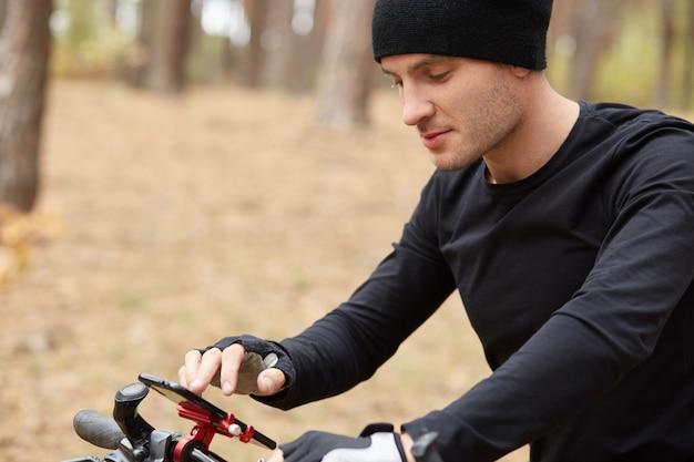 Sluit omhoog openluchtportret van jonge mannelijke fietser gebruikend mobiele telefoon op straat