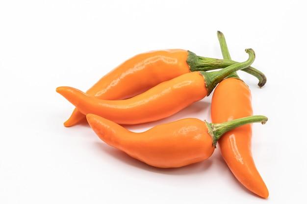 Sluit omhoog oranje spaanse peper op wit.