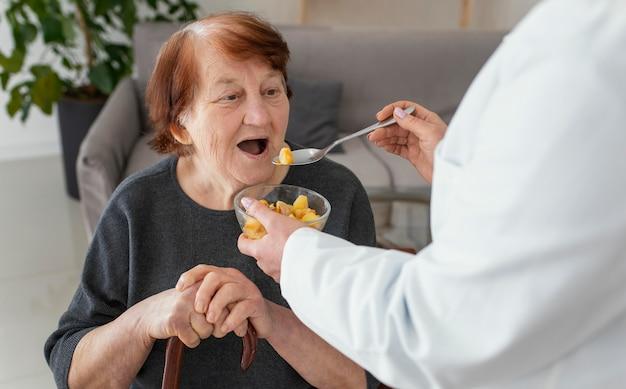 Sluit omhoog oude vrouw die wordt gevoed