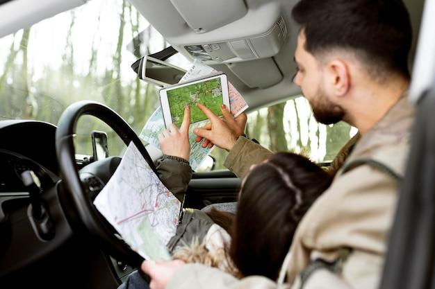 Sluit omhoog paar in auto met kaarten