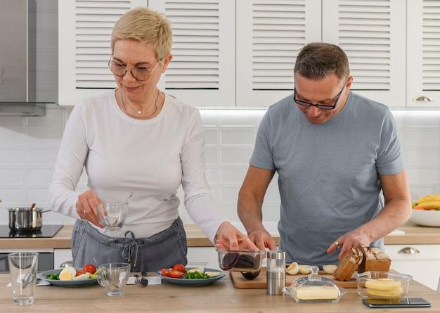 Sluit omhoog paar van middelbare leeftijd die gezond voedsel samen koken