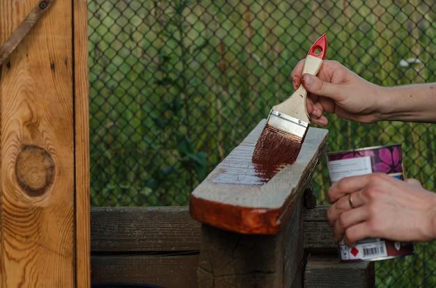 Sluit omhoog penseel in mannelijke hand en schilderend op de houten raad