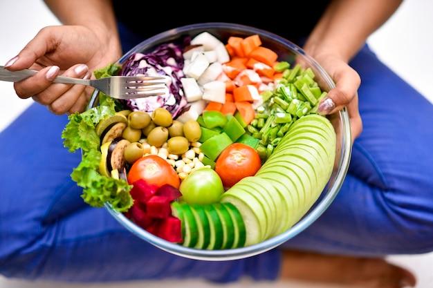 Sluit omhoog persoon die een kom heerlijke groenten houdt