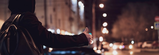 Sluit omhoog persoonshand liftend en wachtend op een autotribune op een weg in de nacht