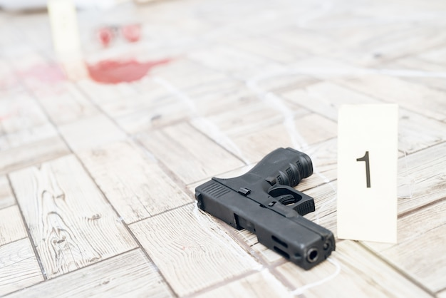 Sluit omhoog pistool bij misdaadscène dichtbij krijtcontour.