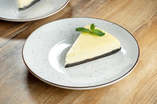 Sluit omhoog plak van delicate airy lime cheesecake op witte plaat. heerlijke dessertcake na het eten.