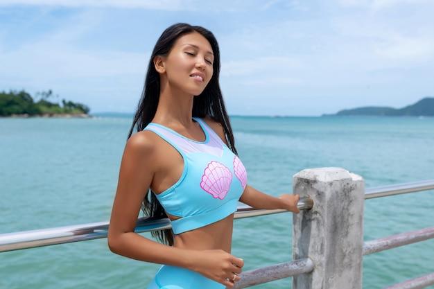 Sluit omhoog portret een jonge glimlachende aziatische vrouw met donker lang haar op houten pijler bij het overzees in de zomerdag. tropische vakantie. zeezicht