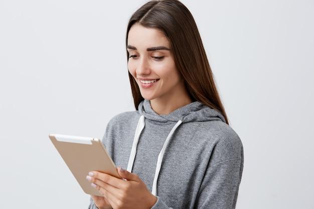 Sluit omhoog portret van aantrekkelijk blij kaukasisch studentenmeisje met donker lang haar n toevallige grijze hoodie houdend digitale tablet in handen, kijkend grappige video's online met gelukkig en ontspannen gezicht