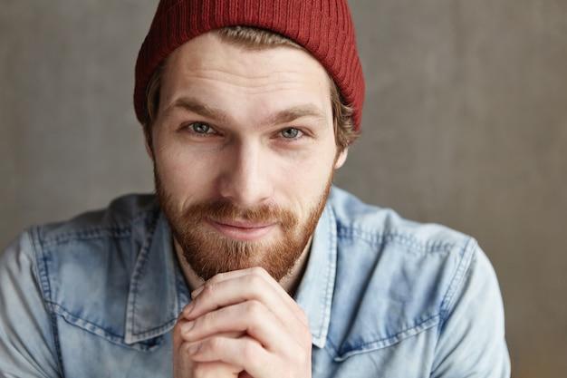 Sluit omhoog portret van aantrekkelijk jong mannetje met dikke baard en charmante blauwe ogen die modieuze kleding dragen, kijkend met flirterige glimlach, houdend handen op zijn kin. mensen en levensstijl