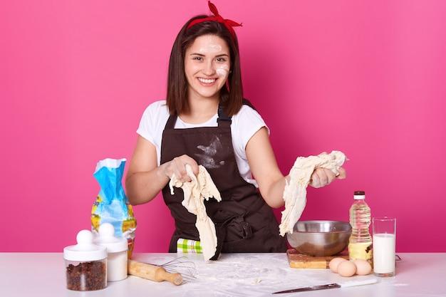 Sluit omhoog portret van aantrekkelijk jong meisje het kneden deeg, makend brood of pizza, bekijkt glimlachend direct camera