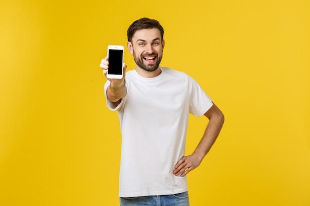 Sluit omhoog portret van aantrekkelijk jong model met trendy kapsel en uitrusting, presenterend nieuwe smartphone voor reclame