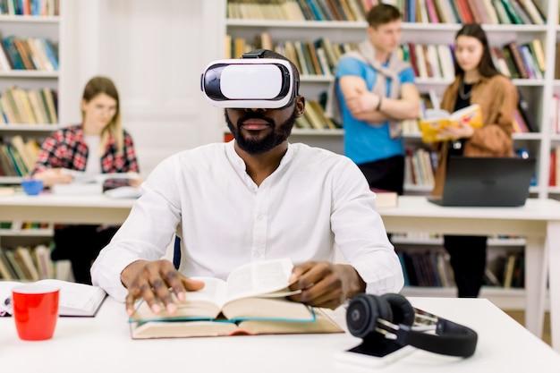 Sluit omhoog portret van aantrekkelijke gerichte jonge afrikaanse amerikaanse gebaarde studentenzitting in bibliotheek en lezingsboek in vrbeschermende brillen, terwijl zijn groepsgenoten die op de ruimte spreken