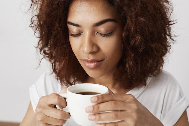 Sluit omhoog portret van afrikaanse de kop ruikende koffie van de meisjesholding met gesloten ogen. 's ochtends wakker worden is moeilijk voor volwassenen.